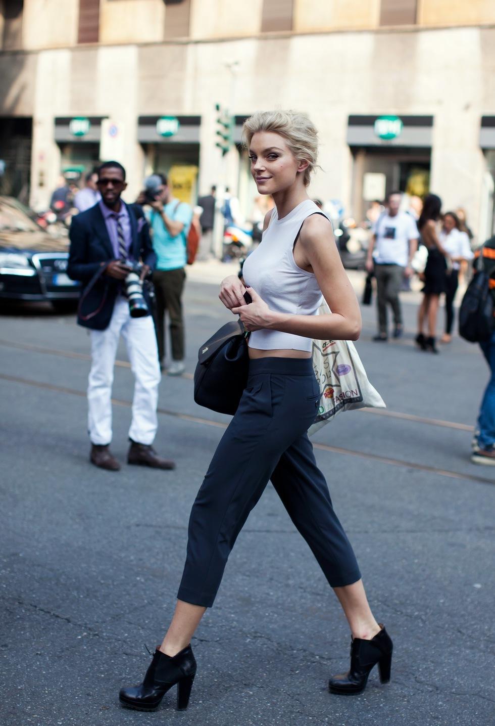 На фото: укороченные черные брюки с светлой блузкой.