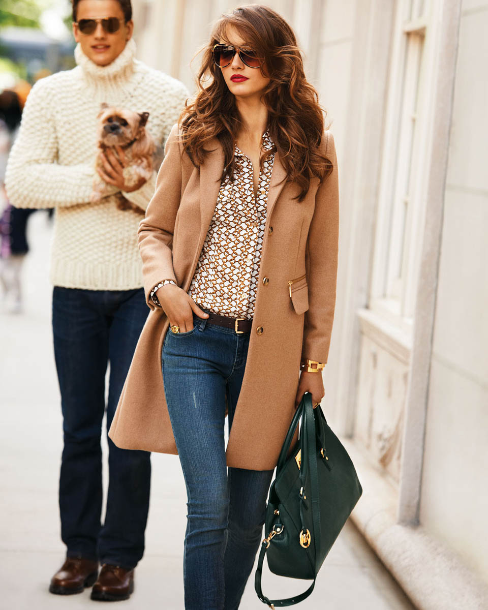 На фото: джинсы с блузой и светлым пальто.