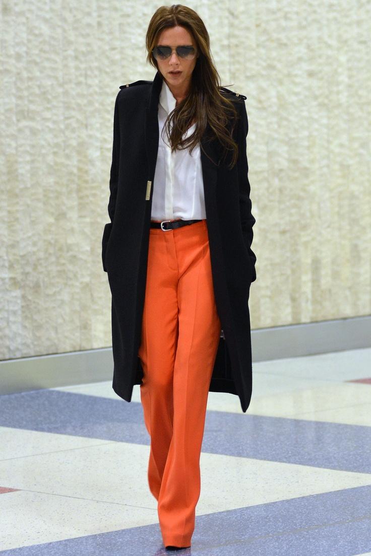 На фото: черное пальто. белая блуза и брюки оранжевого цвета.