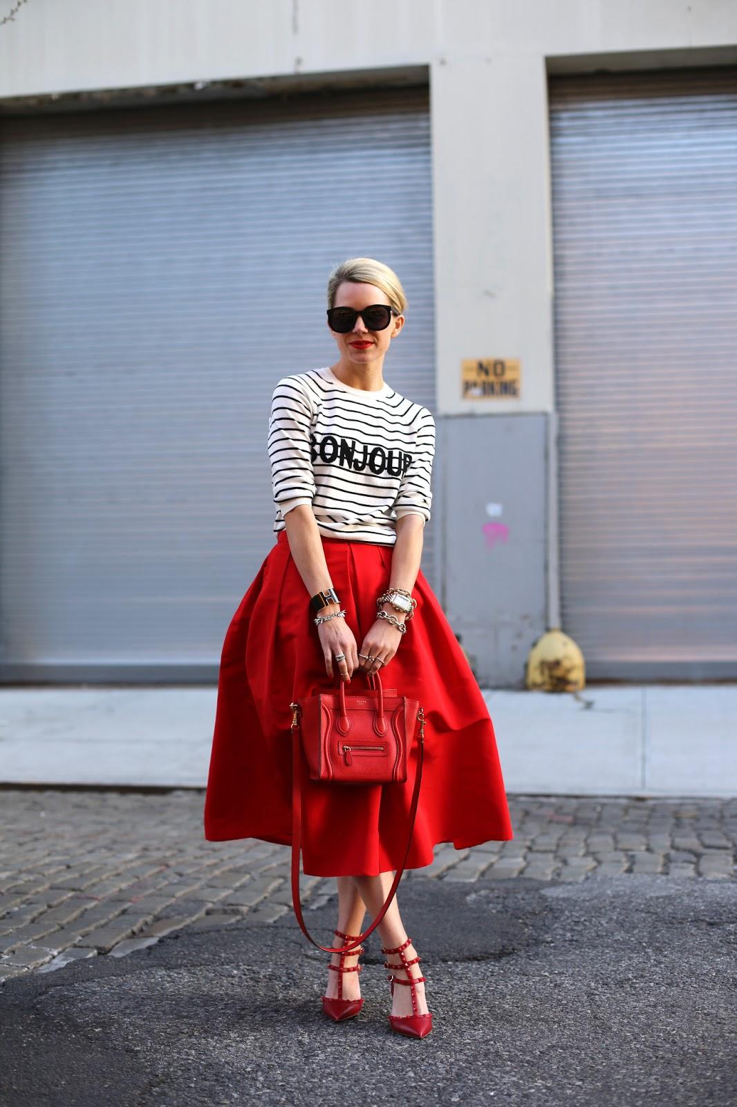 На фото: кофта с принтом в полоску с красной юбкой, красной сумкой и красных туфлях.