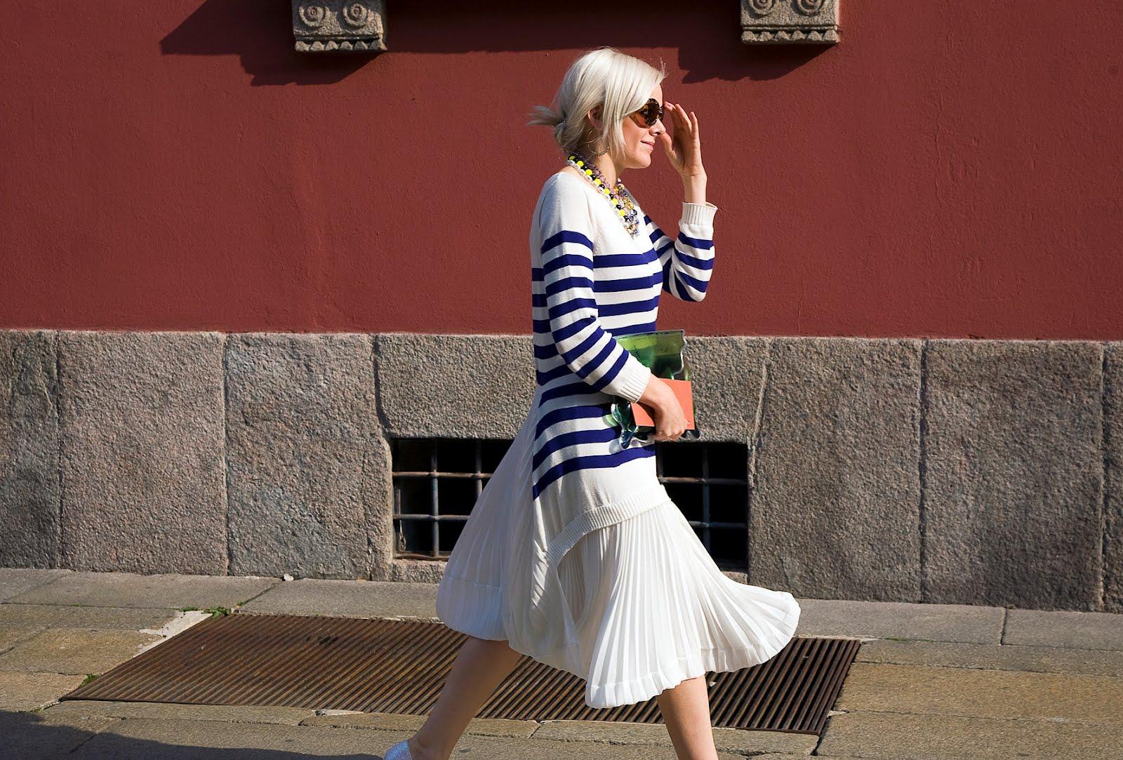 На фото: белый свитер с принтом в черную полоску с белой юбкой.