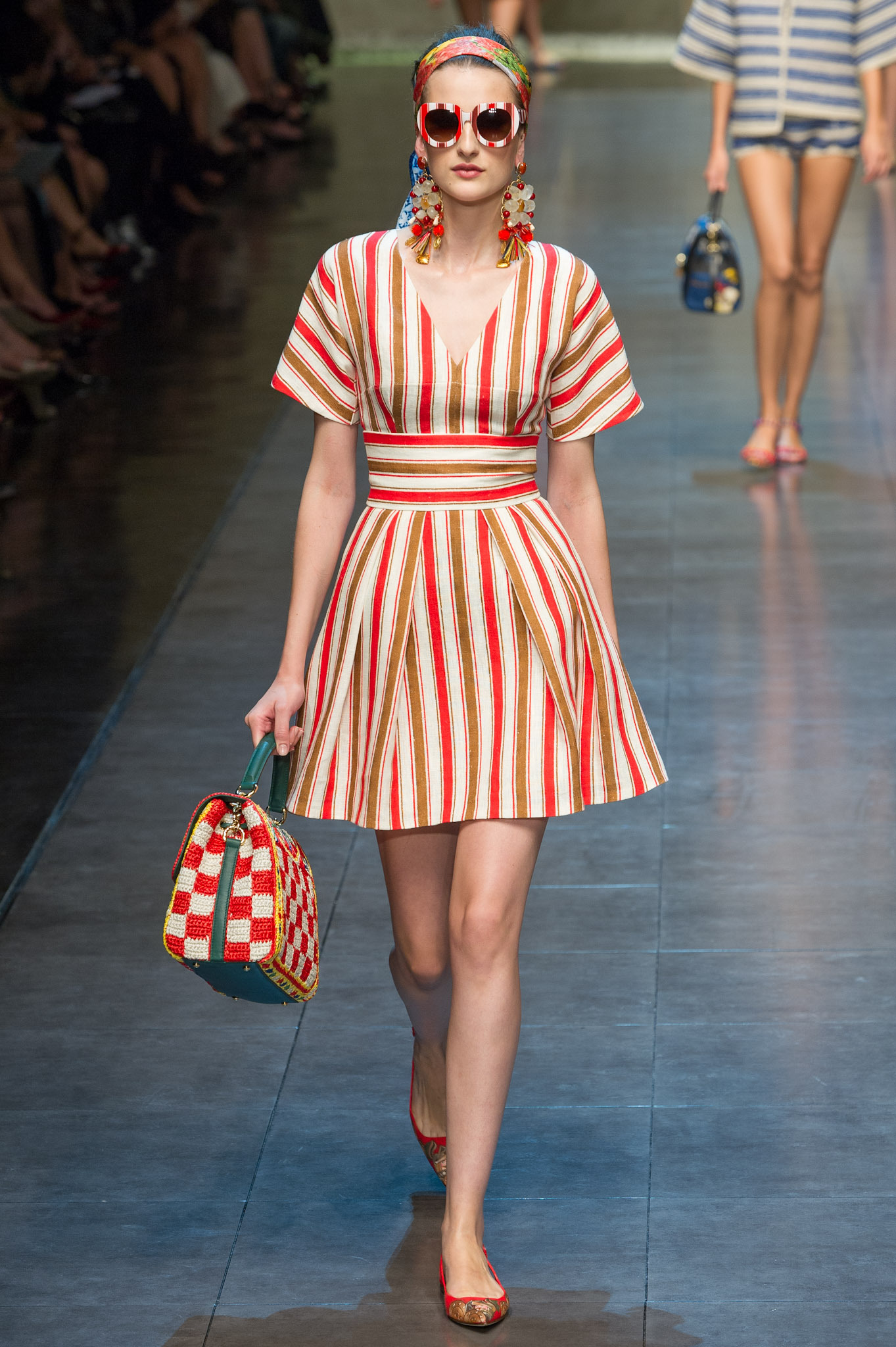 На фото: платье в вертикальную красную полоску с красно белой сумкой и красных босоножках.