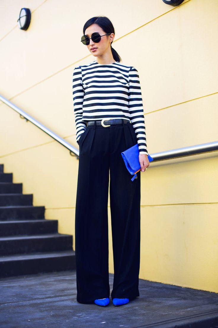 На фото: блузка с принтом в полоску с черными расклешенными брюками.