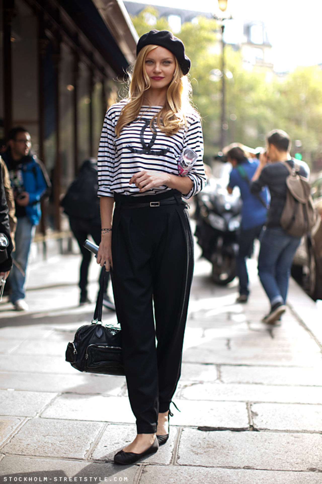 На фото: кофта с принтом в полоску и в черных брюках, сумкой и туфлях балетках.