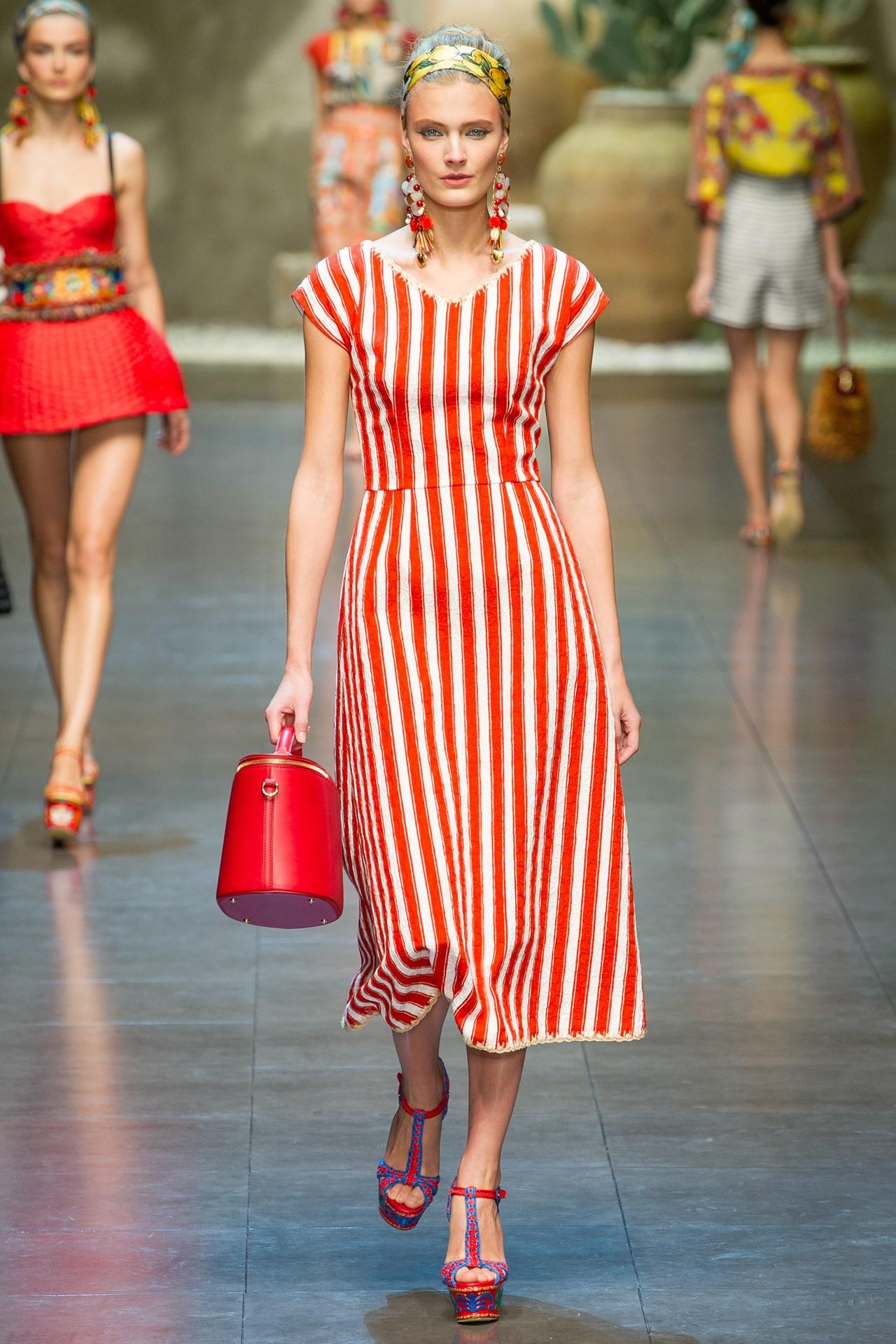 На фото: платье в вертикальную красную полоску с красной сумкой и красных босоножках.
