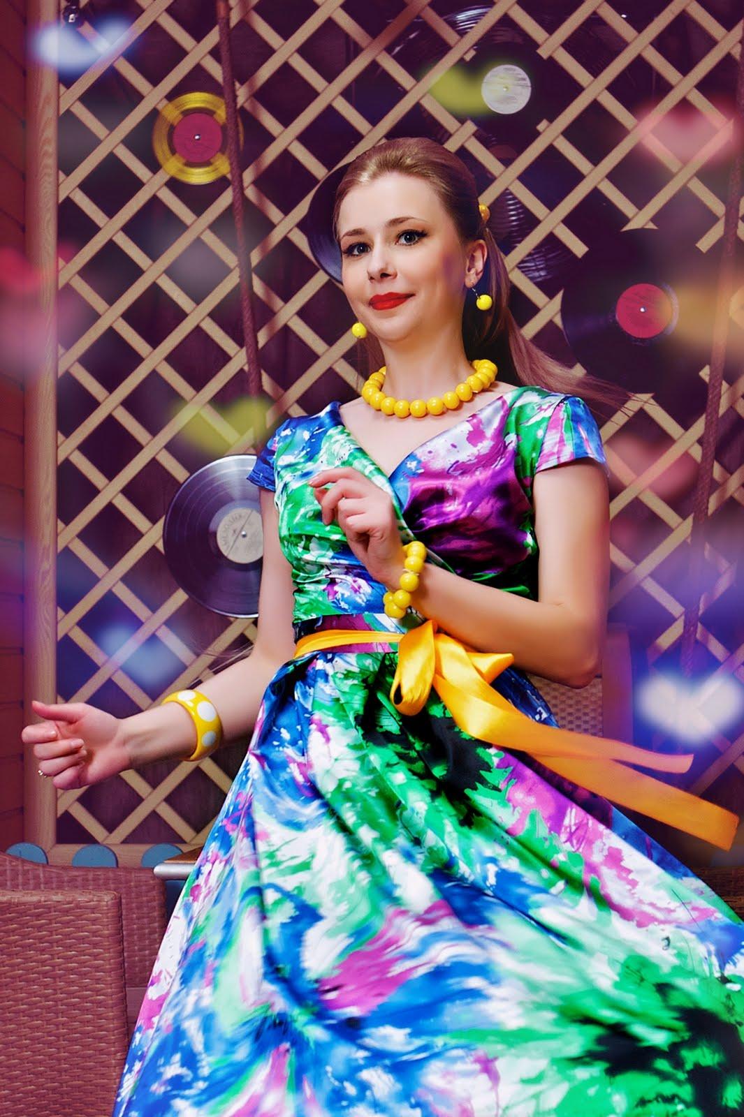 На фото: яркое разноцветное платье в стиле стиляг с желтыми бусами, браслетом и поясом.