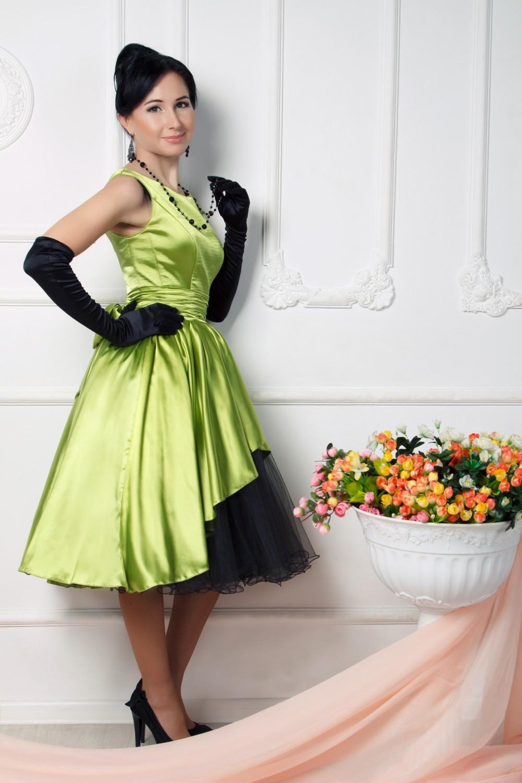 На фото: яркое платье нежно салатового цвета с черными высокими перчатками.