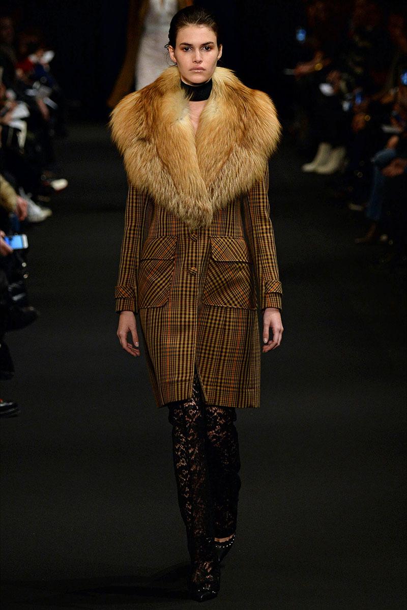 Необычная модель женского пальто в клетку с меховым воротником