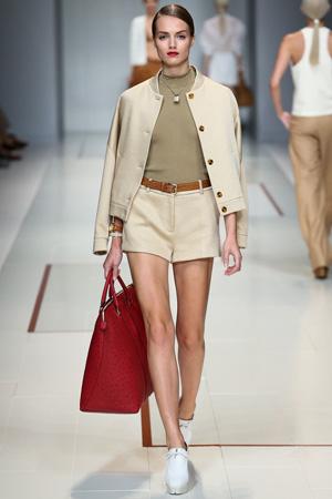 На фото: модная бежевая куртка бомбер весна лето 2015 с шортами и большой модной сумкой весна лето 2015 – Trussardi
