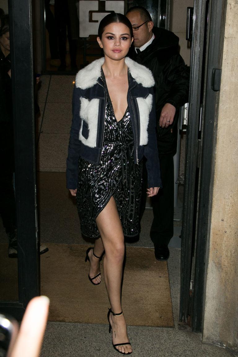 Блестящее платье до колена Селены Гомес , легкие босоножки и куртка-косуха