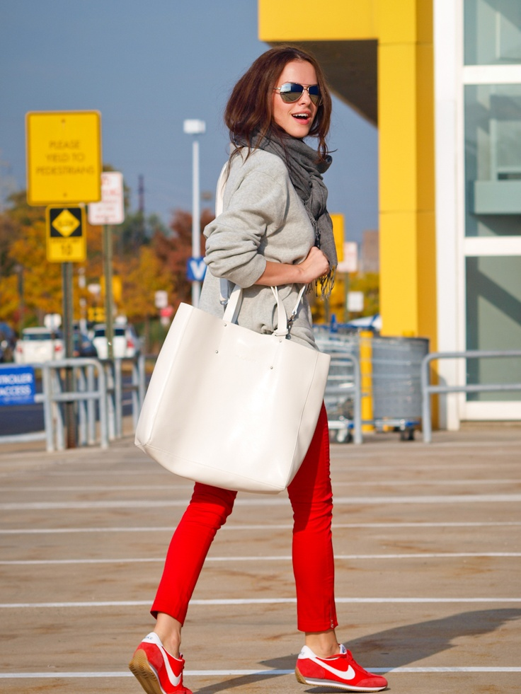 Красные брюки с серым джемпером и белой сумкой.