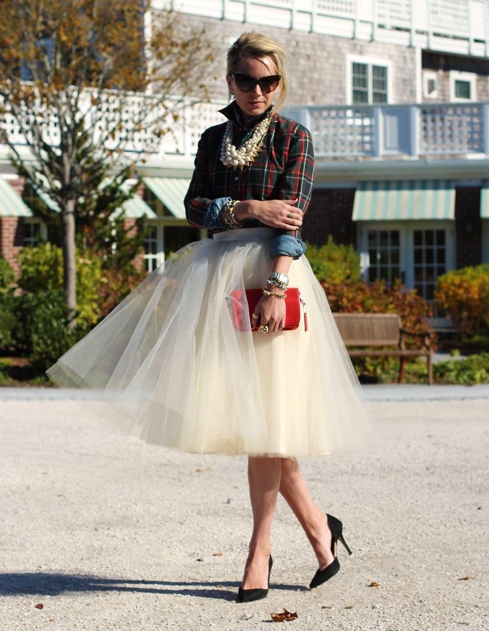 Многослойная белая юбка с блузой в клетку.