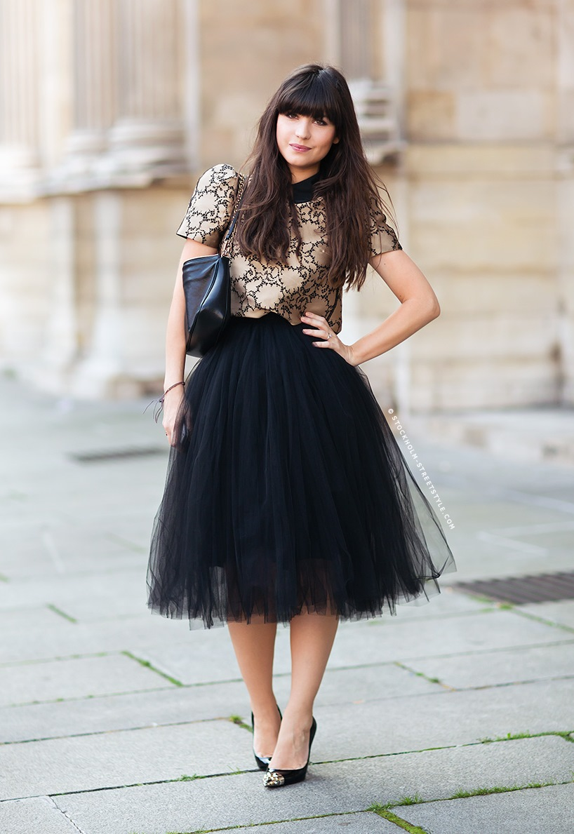 Многослойная черная юбка с белым топом.
