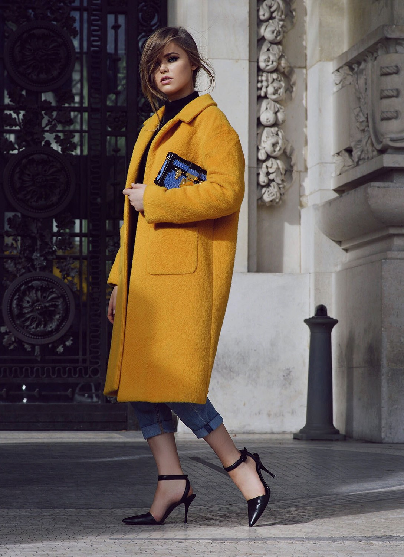 Оранжевое пальто оверсайз с джинсами с отворотами.