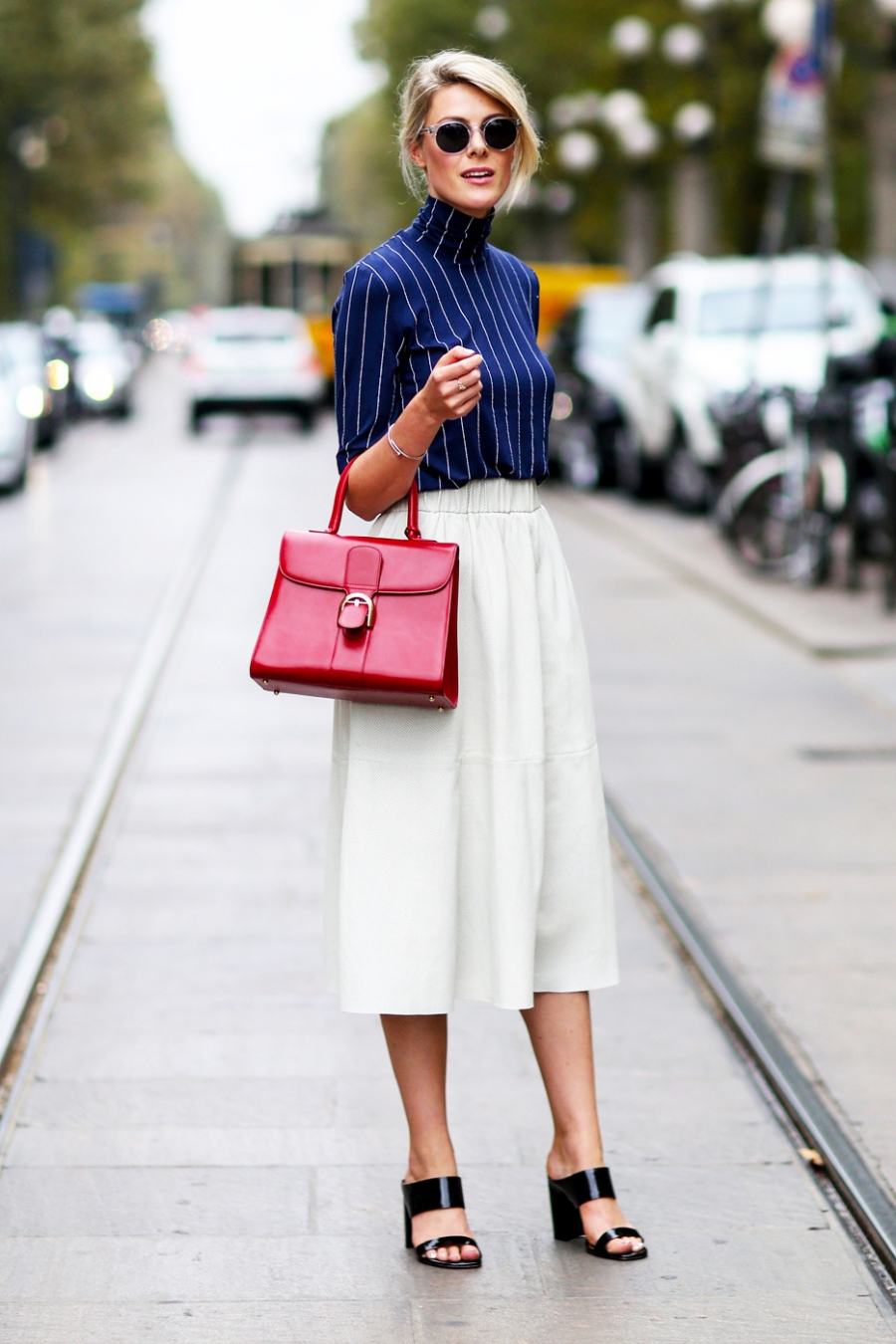 Белая юбка темно синего цвета и красная сумка.