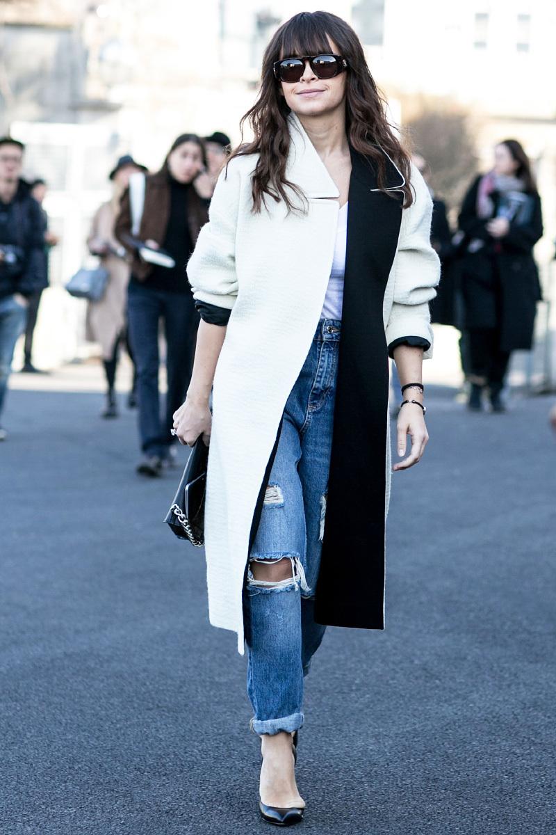 Белое пальто с рваными синими джинсами.