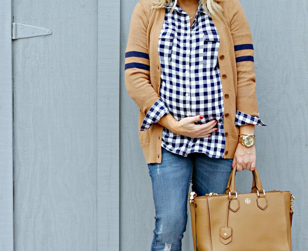 Прямые синие джинсы с небольшими потёртостями и рубашка-блуза на пуговицах с закруглённым подолом, выпущенная наверх.