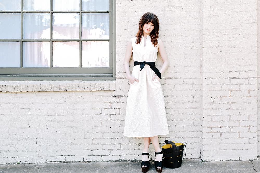 Универсальный белый цвет - белое платье дополнено черным ремешком, босоножками и сумкой.