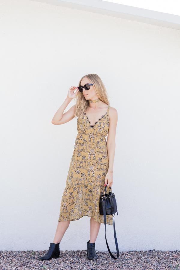 Платье-сарафан приглушённо жёлтого цвета, чёрно-белые узоры, раскинутые по всему платью и брутальные кожаные ботики.