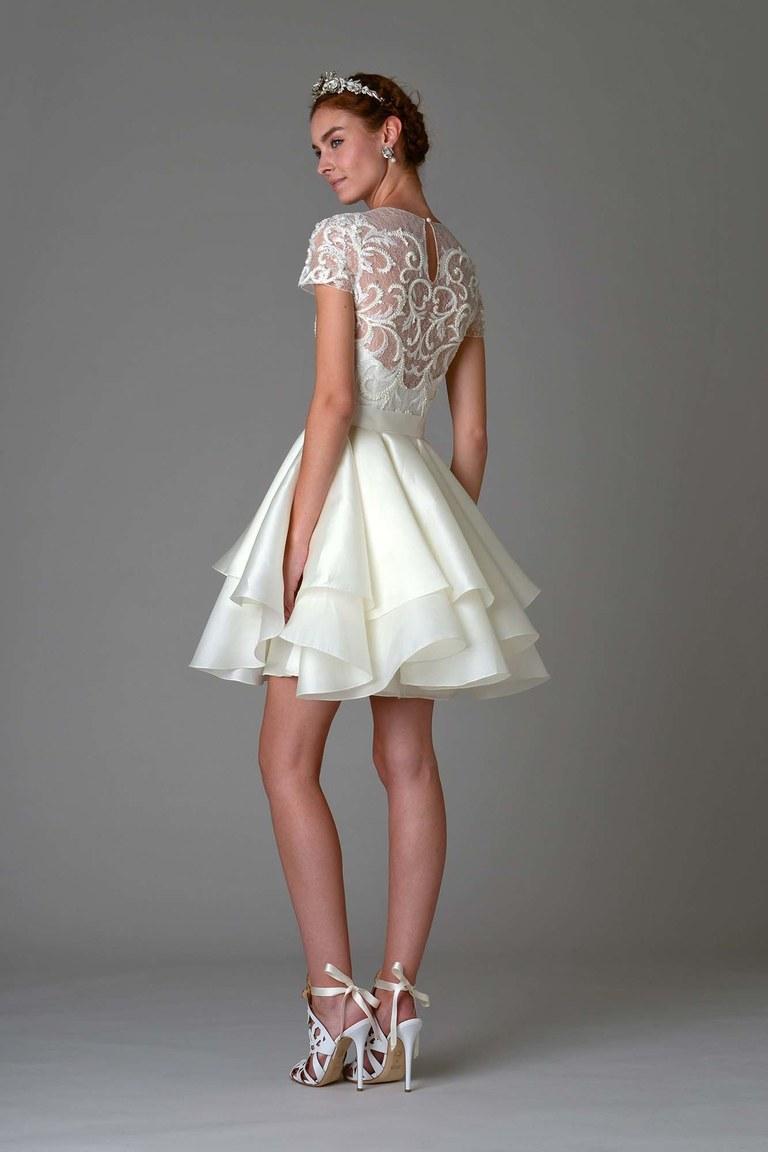 Короткое многослойное белое свадебное платье с кружевным орнаментом на спине из коллекции Marchesa.