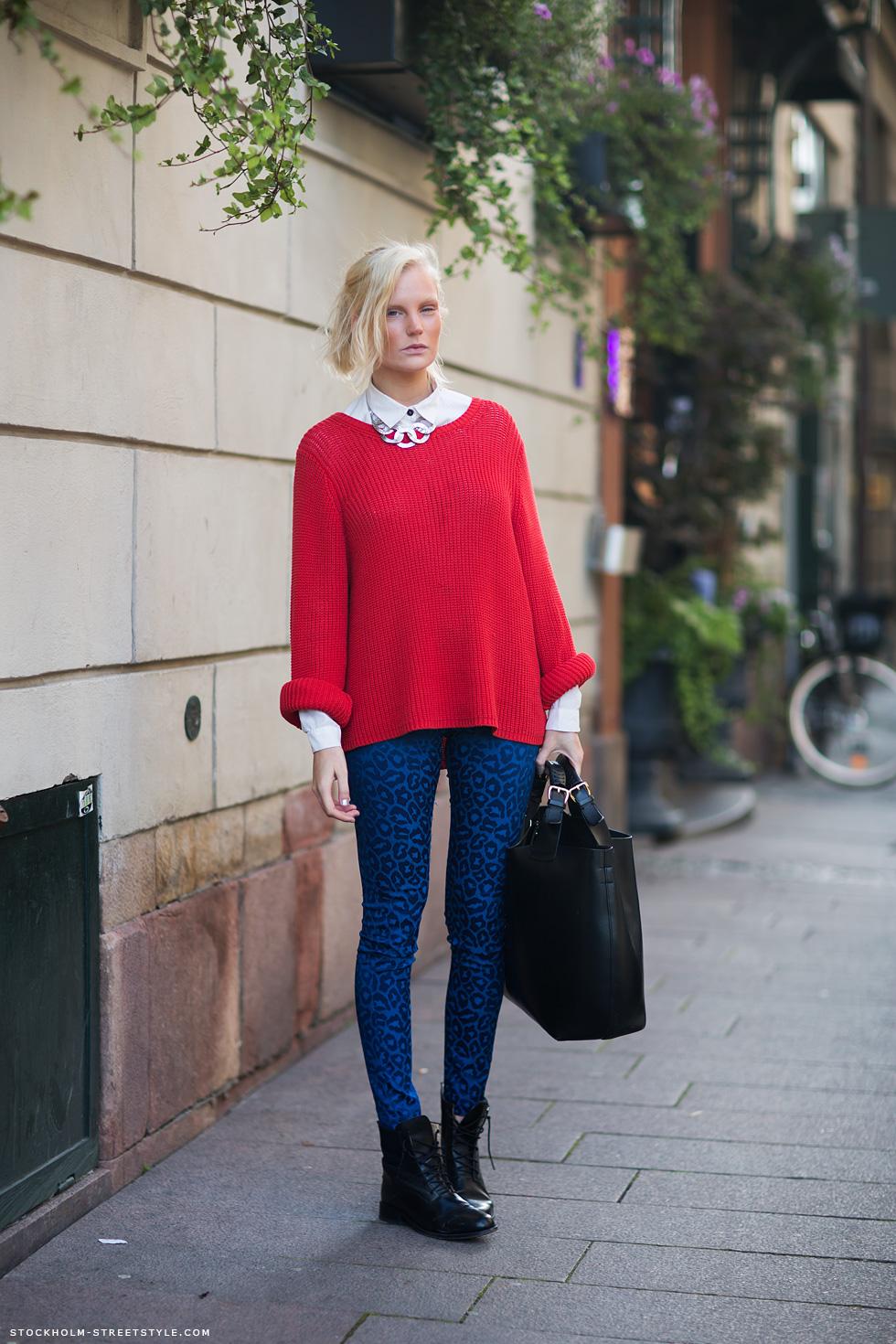 На фото: узкие синии джинсы с красного цвета кофтой длиной до линии бедра.
