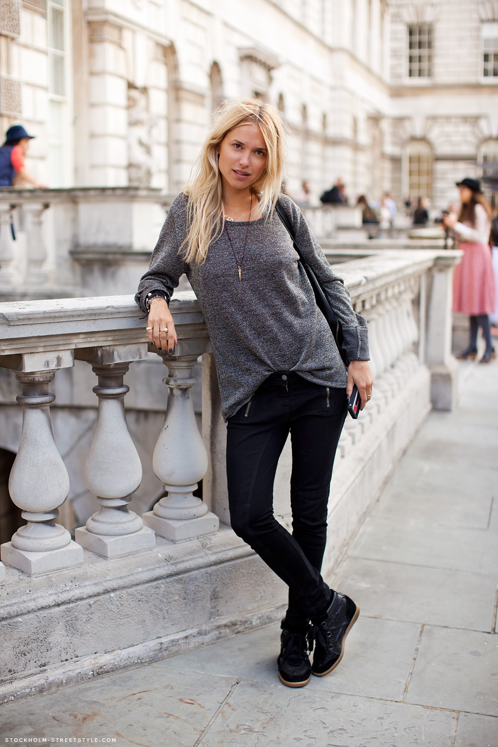 На фото: узкие черные джинсы с теьной кофтой длиной до линии бедра.