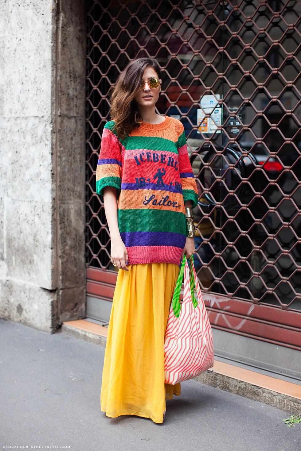 Яркий разноцветный свитер длиной до линии бедра с яркой желтой длтнной юбкой.
