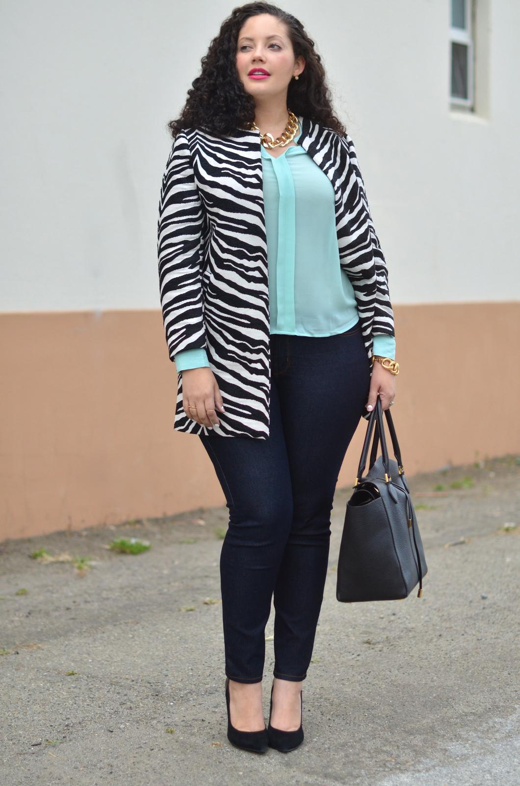 На фото: узкие черные джинсы с лилового цвета блузкой чуть ниже талии и кардиганом длиной до линии бедра.