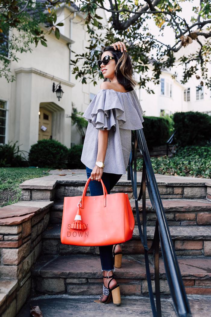 Топ с открытыми плечами нейтрального серого цвета, босоножками на массивном каблуке и яркая красная большая сумка.