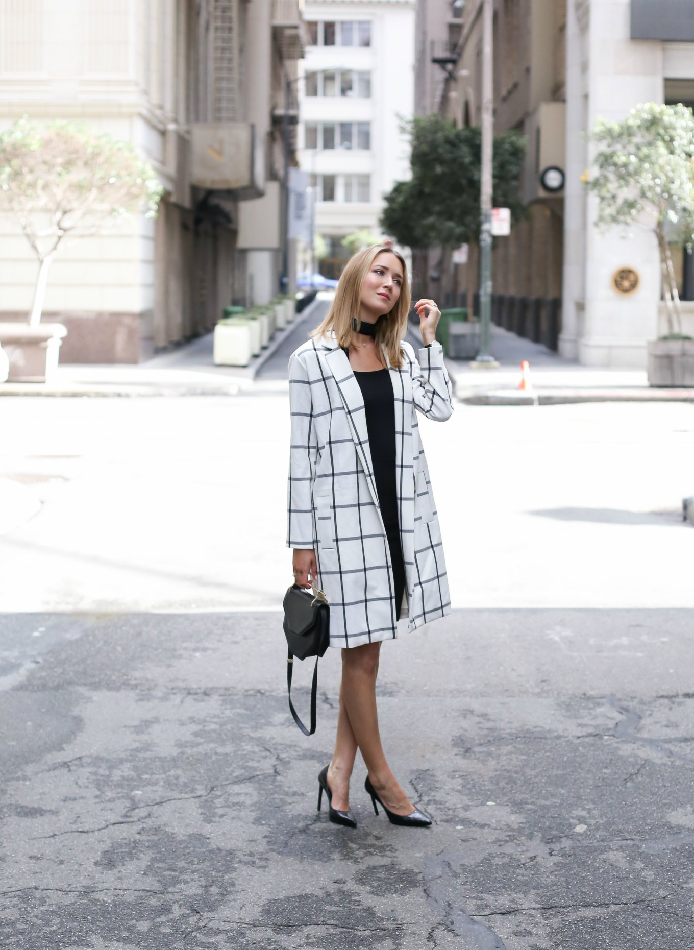 Офисный стиль состоит из лаконичного платья - футляра черного цвета , белого тренча в широкую клетку, классические лакированные туфли и сумки.