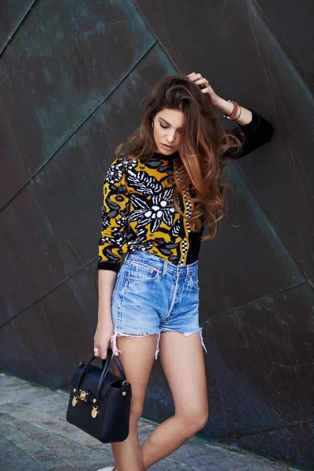 На фото: джинсовые шорты с кофтой с принтом.