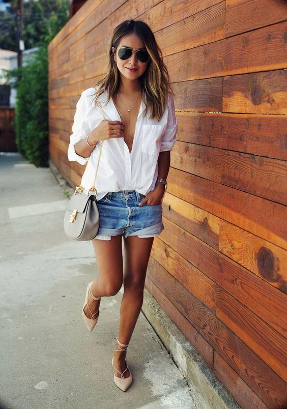 На фото: рваные джинсовые шорты с белой рубашкой.