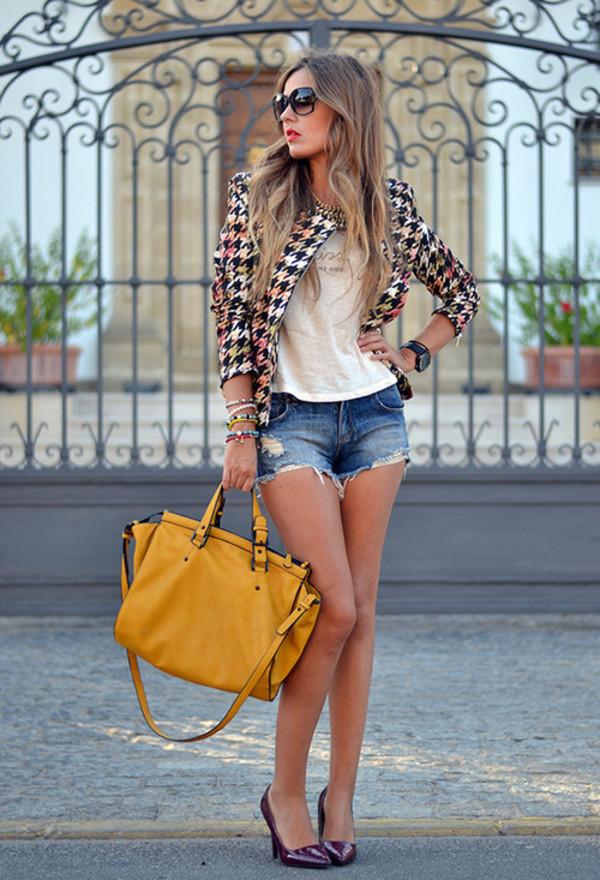 На фото: потертые джинсовые шорты с белым топиком и пиджком и туфлях на высоком каблуке..