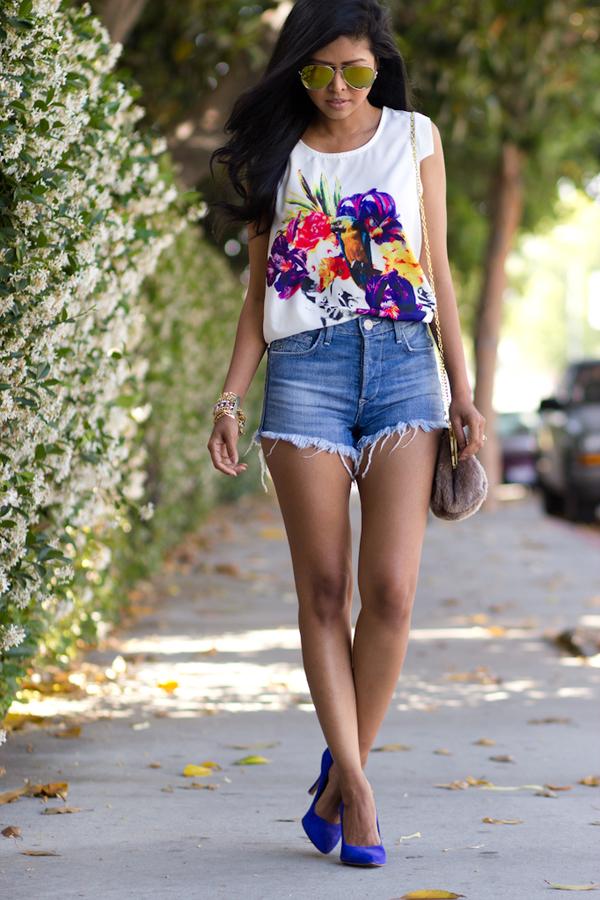 На фото: джинсовые шорты с белым топиком с ярким принтом.