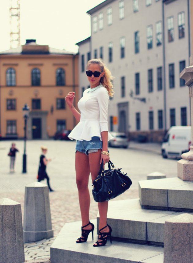 На фото: джинсовые шорты с белой блузкой и в туфлях на высоком каблуке.