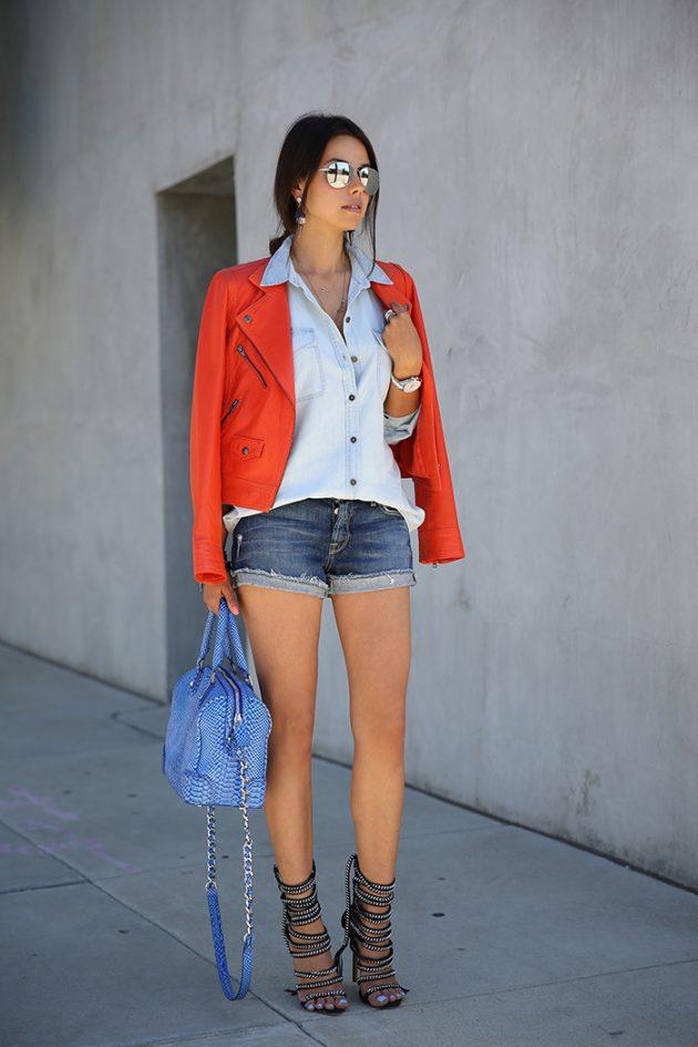На фото: короткие джинсовые шорты с голубой блузкой и красным пиджаком.
