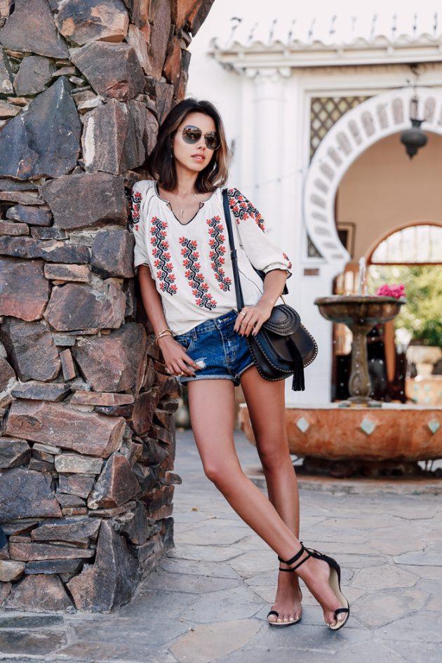 На фото: короткие джинсовые шорты с белой блузкой с цветочным принтом.