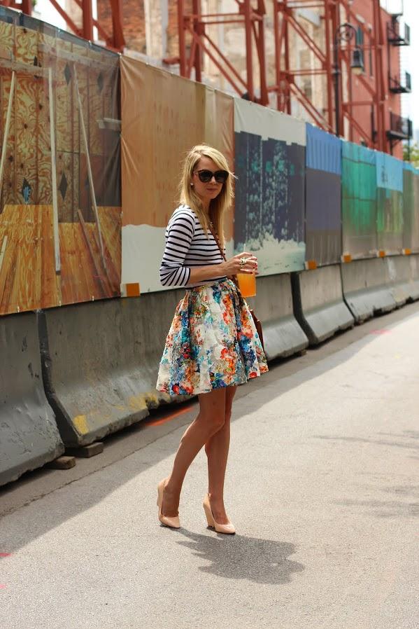 На фото: короткая пышная юбка с ярким цветочным принтом с блузкой в полоску.