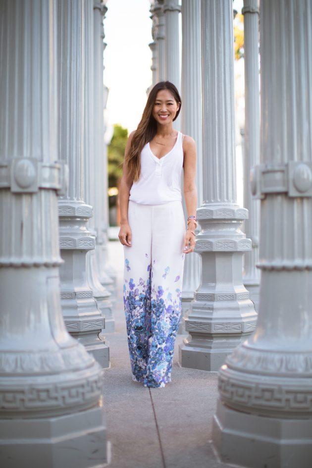 На фото: белые брюки Палаццо с принтом и белой блузой.