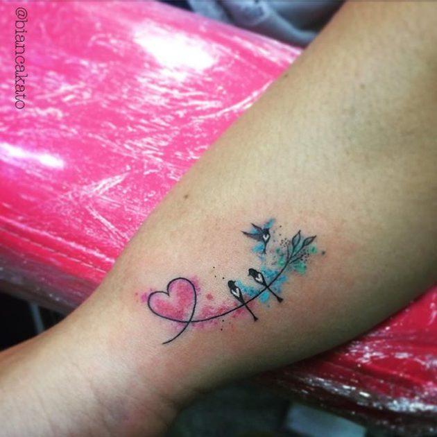 На фото: акварельная татуировка в виде сердца и птичек.