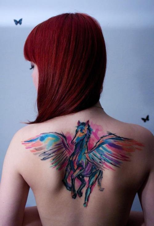 На фото: акварельная татуировка в виде яркой разноцветного коня с крыльями на спине.