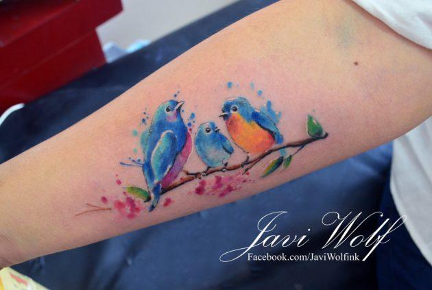 На фото: акварельная татуировка в виде ярких птиц на ветке.