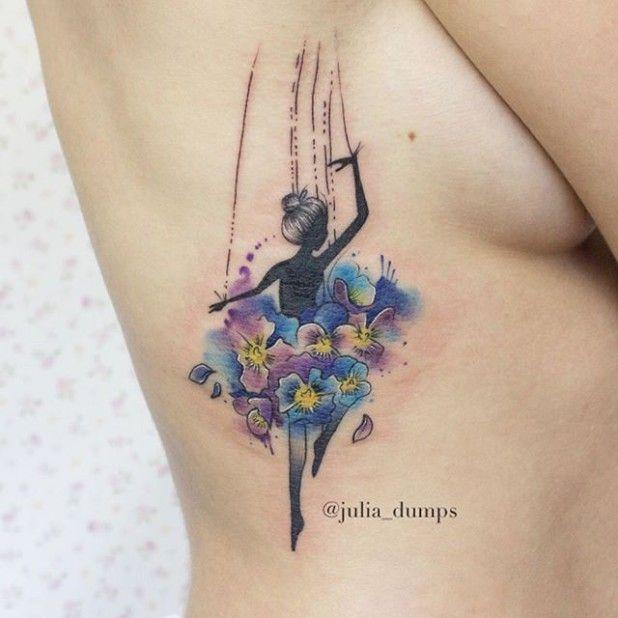 На фото: акварельная татуировка в виде яркой разноцветного танцующей девушки на правой стороне спины.
