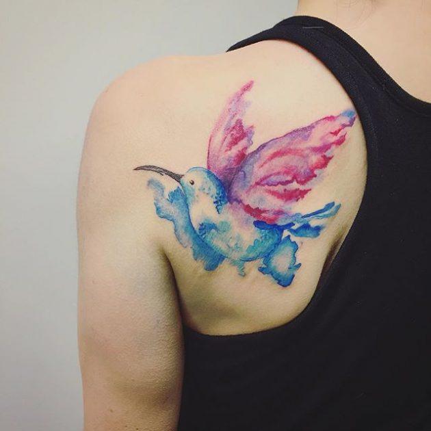 На фото: акварельная татуировка в виде яркой птицы на спине.