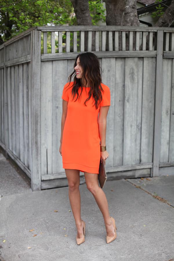 На фото: оранжевое платье прямого покроя, длиной выше колена с коротким рукавом.