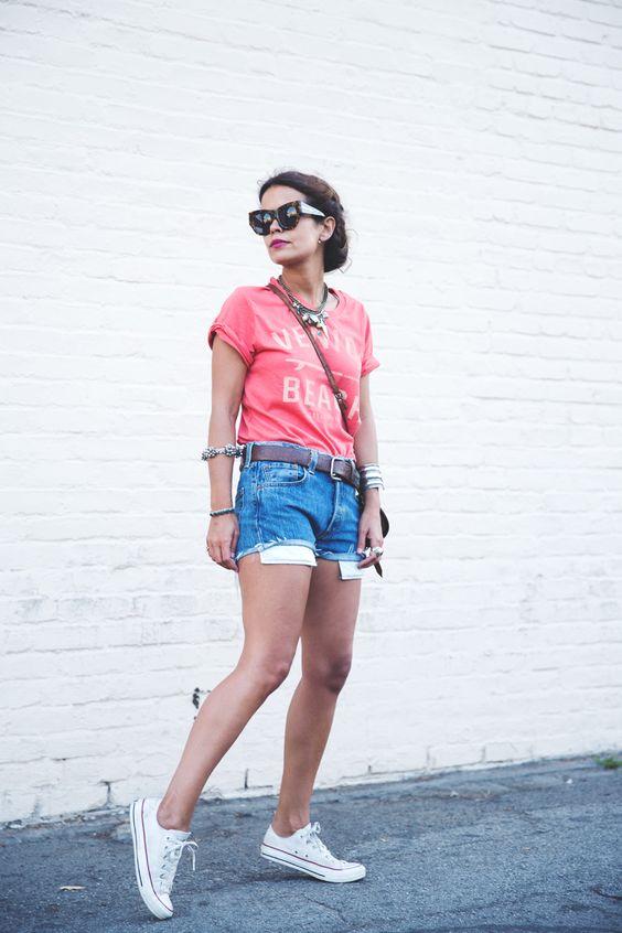 На фото: белые кеды Converse в сочетании с шортами и блузой.