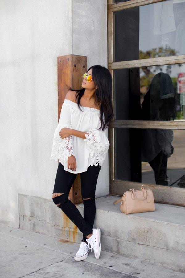 На фото: белые кеды Converse в сочетании с черными рваными джинсами и блузой.
