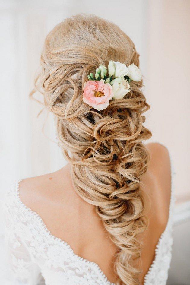 На фото: свадебная прическа - объемная косы на длинных волосах, украшенная цветами.