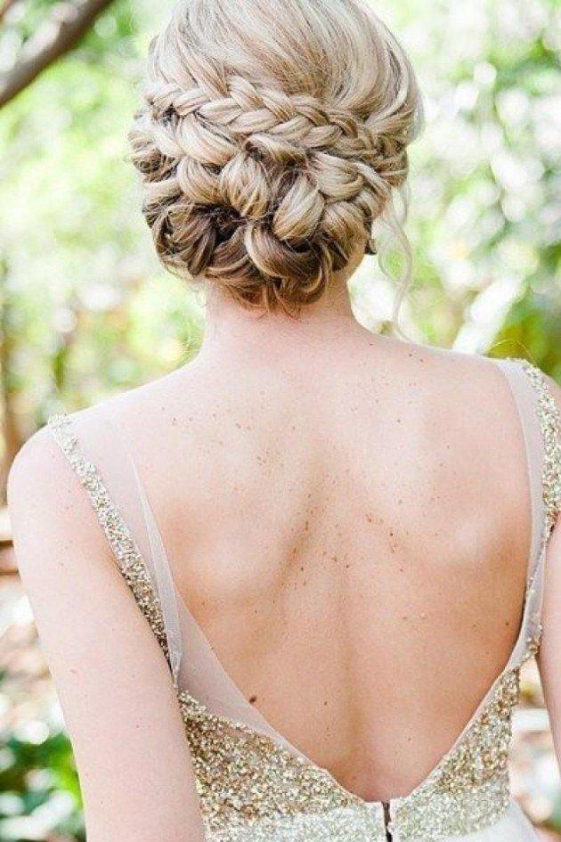 На фото: свадебная прическа - объемная косы на длинных волосах, уложенные в пучек - летний вариант прически.