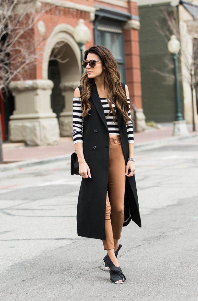 На фото: длинный жилет черного цвета в сочетании с брюками песочного цвета и кофтой в полоску.